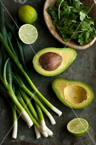 Ingredients for guacamole: avocado, spring onions, limes and coriander