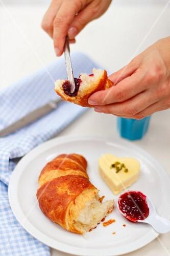 A hand spreading jam on a croissant