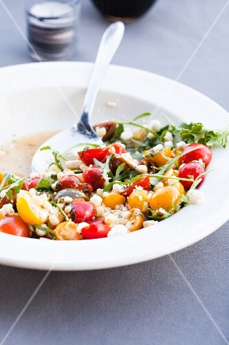 Cherry Tomato Salad with Corn and Ricotta and Arugula in a White Bowl