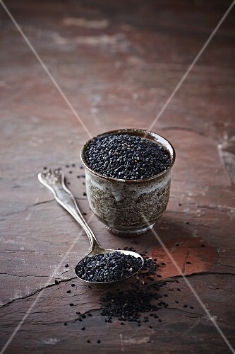 Black sesame seeds on a spoon and in a pot