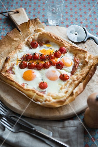 Puff pastry pizza with fried eggs and tomatoes, for breakfast