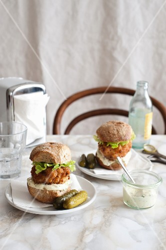 Fish cakes in burger buns with pickled gherkins and tartare sauce, in a restaurant