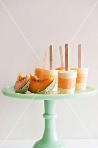 Melon ice lollies and fresh melon wedges on a cake stand