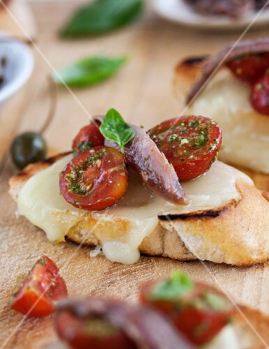 Cheese on toast made with mozzarella, tomatoes and anchovies