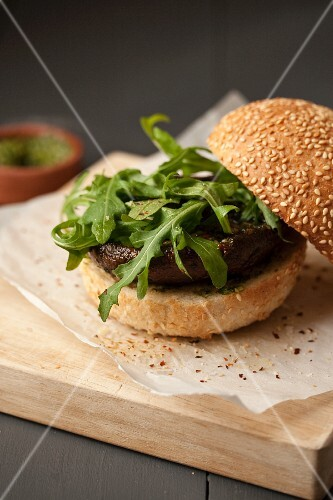 A burger bun filled with mushrooms and rocket