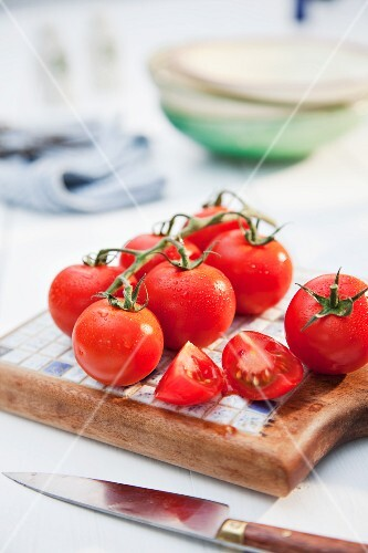 Tomatoes on a board with a knife