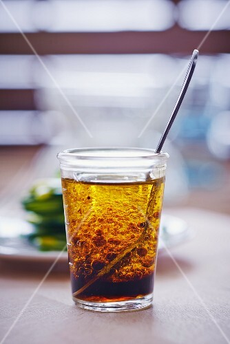 Vinaigrette in a glass with a spoon