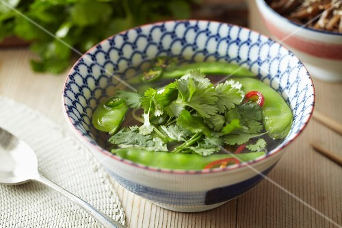 Noodle soup with mange tout and coriander leaves (Asia)