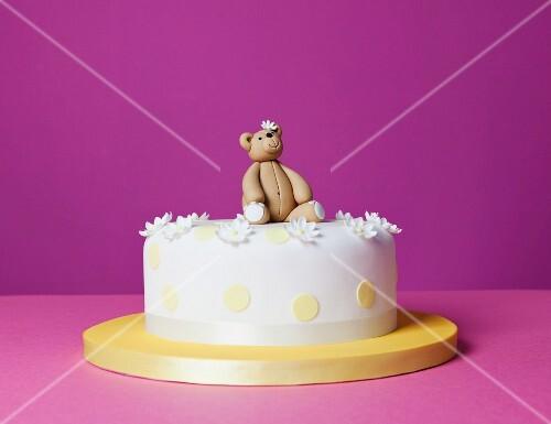 A teddy bear cake with sugar flowers
