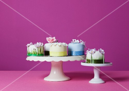 Several small celebration cakes on cake stands