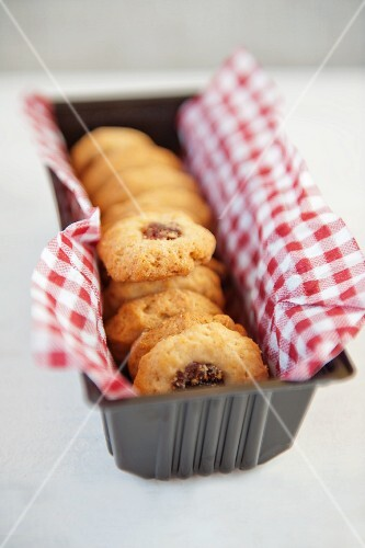 Jam biscuits on a checked napkin in a loaf tin