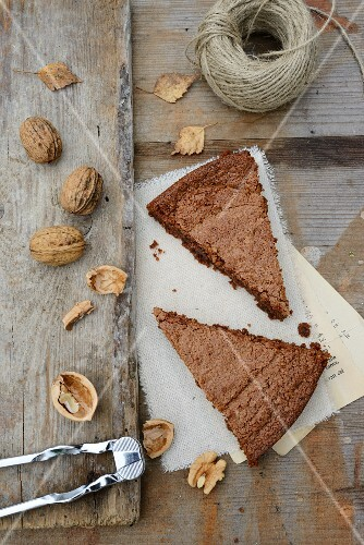 Two slices of chocolate & walnut cake, walnuts, a nutcracker and a roll of twine