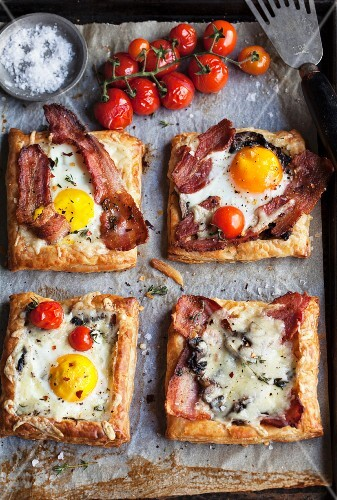 Puff pastry slices topped with bacon, fried egg, tomatoes and cheese
