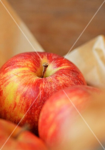 a red apple wrapped in brown wax paper (close up)