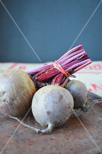 A bunch of raw beetroots on a rusted metal tray