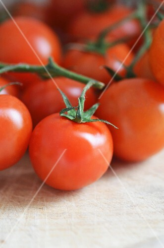 Fresh vine tomatoes on a wooden chopping board (close up)