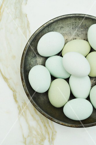 A pewter bowl filled with blue eggs on a white marble surface