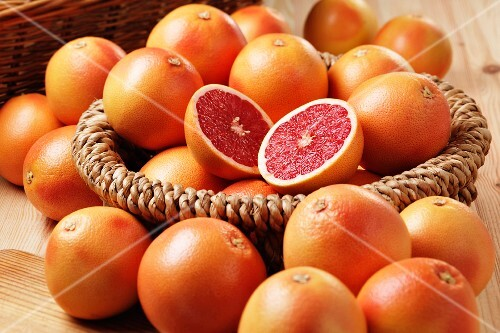 Pink grapefruit in a basket and around the outside