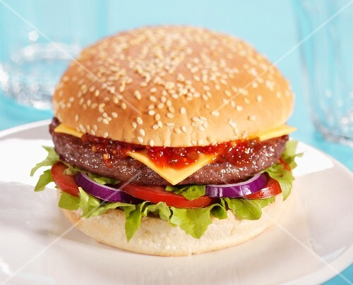 Cheeseburger with tomatoes, onions, lettuce and ketchup