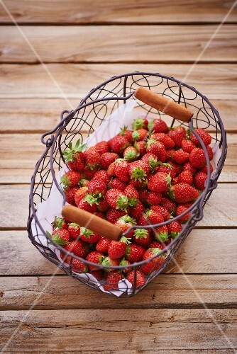 Lots of fresh strawberries in a wire basket