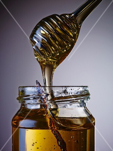 Vanilla honey in a jar and on a honey spoon