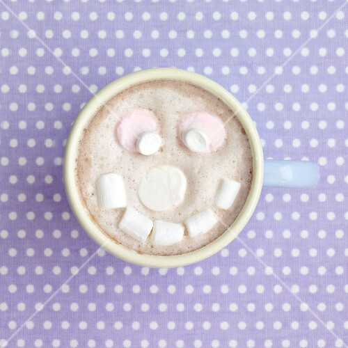 A cup of cocoa with a marshmallow face