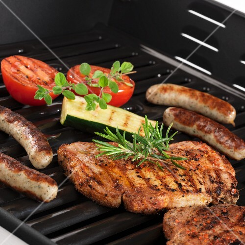 Pork steaks, sausages and vegetables on the grill