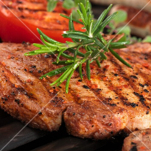 Grilled pork steak with fresh rosemary (close-up)