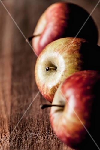 Three apples in a line on a wooden surface
