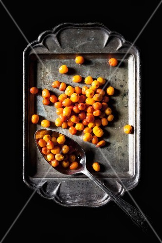 Sea buckthorn berries on an old metal tray (view from above)