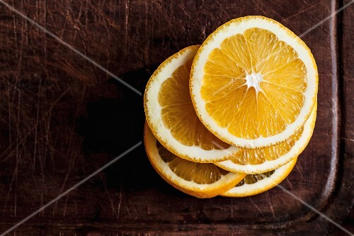 A stack of orange slices on a wooden chopping board