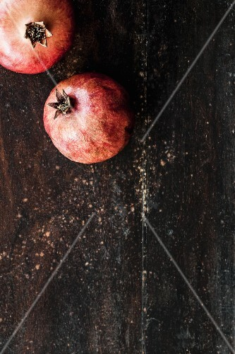 Two pomegranates on a wooden surface (view from above)