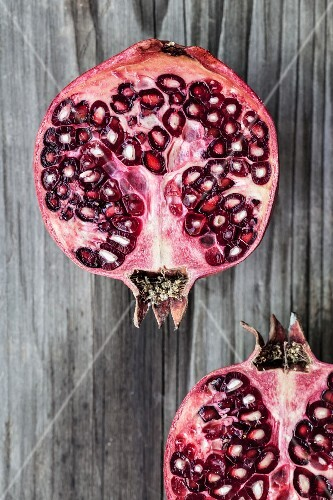 Two pomegranate halves on a wooden surface (view from above)