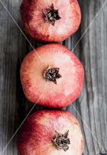 Three pomegranates on a wooden surface