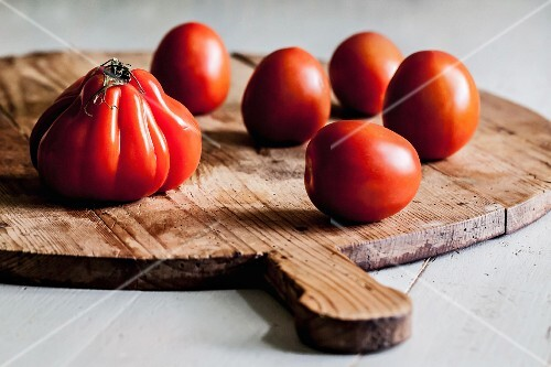 Several tomatoes on a round wooden board