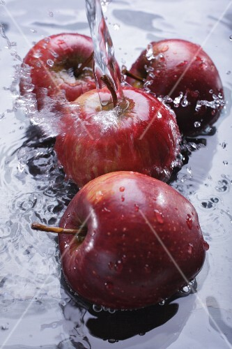 Red apples in water with a jet of water