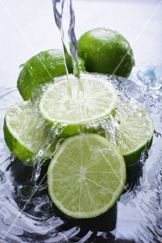 Limes in water with a jet of water