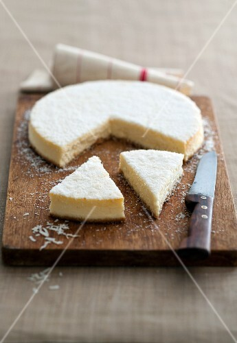 Cheesecake with grated coconut, partly sliced, on a chopping board