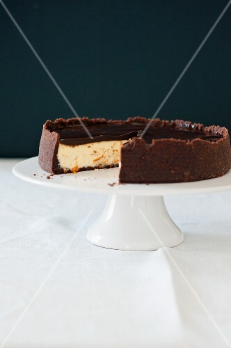 Cheesecake with oranges and chocolate on a cake stand