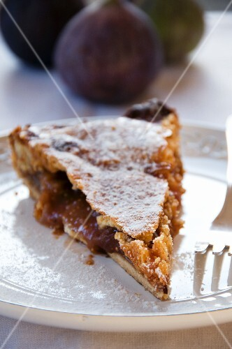 A slice of fig cake with icing sugar