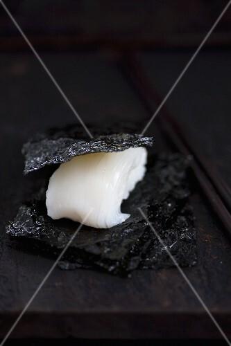 Nigiri sushi with squid (tai) between pieces of salty nori (Japan)