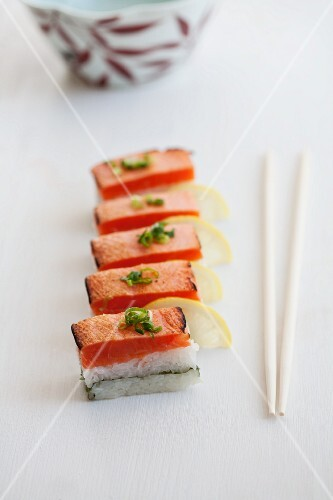 Oshi sushi with seared salmon, sliced spring onions (negi) and lemons (Japan)