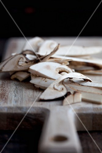 Sliced matsutake mushrooms on a chopping board