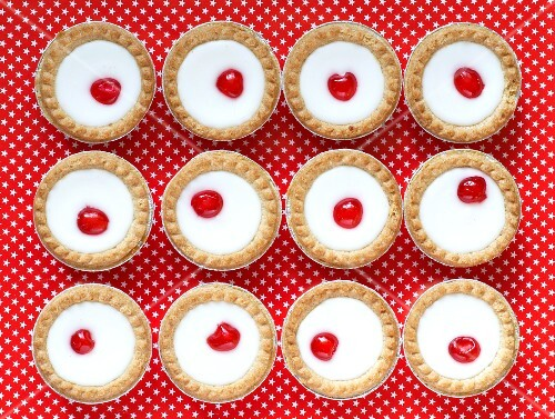 Lemon tarts topped with glacé cherries
