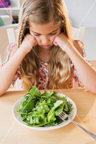 Mädchen sitzt schlecht gelaunt vor Teller mit Salat
