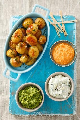 Baked potatoes with three dips (pea dip, carrot dip, tzatziki)