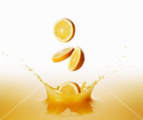 Oranges falling into orange juice