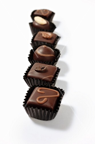 A row of assorted filled chocolates in paper cases