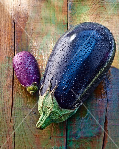 Two aubergines (large and small) on a wooden surface