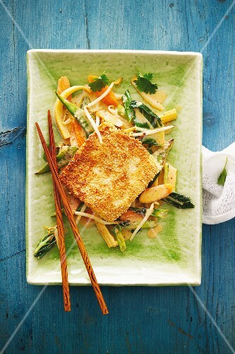 Tofu with a sesame crust on a bed of vegetables